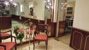 Rezeptionsbereich des Hotels mit vielen Spiegeln und Sitzgelegenheit
