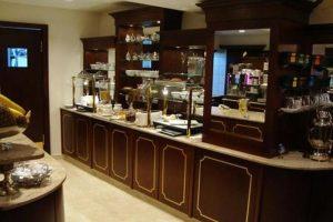 Dunkle Holztheke mit Marmoroberlfäche - das Frühstücksbuffet des Hotels