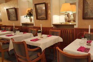 Drei Tische mit weißer Tischdecke, alte Bilder und Leuchter an der Wand.