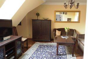 Blick in Appartement 17 - rechts Couch, hinten gold umrandeter Spiegl und kleiner Schrank, links TV-Schränkchen