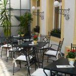 Blick auf die Dachterrasse: mehrere Tische mit Stühlen, hinten Palme