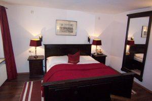 Zimmer mit Bett, Nachttischchen und Spiegel - dunkles Holz und rote Tagesdecke