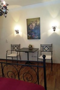 Sitzgruppe aus quadratischem Tischchen und Metallstühlen, an Wand Bild und Lampen
