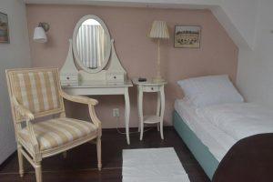 Blick in Zimmer 8 mit Bett, Stuhl und Schminktischchen