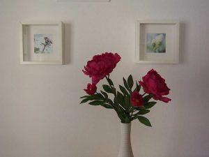 Rote Blumen vor zwei Bildern an der Wand