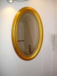 Gold gerahmter, ovaler Spiegel an der Wand