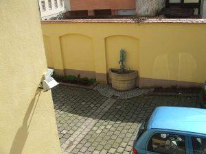 Blick in den Innenhof mit gepflastertem Bogen und kleinem Brunnen