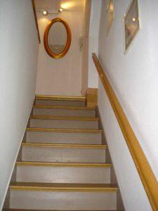 Stufen nach oben mit goldfarbenem Handlauf und Spiegel