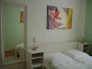 Bett mit Spiegel und Bild an der Wand