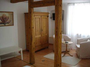 Sitzecke, alter Holzschrank und Balken aus dem Fachwerkbau
