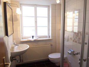 Fenster, links Waschbecken, rechts Toilette und Dusche