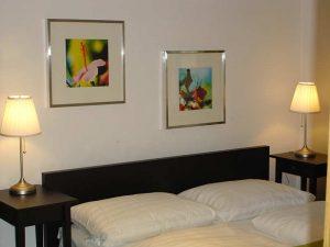 Doppelbett mit zwei Leuchten und Bildern an der Wand