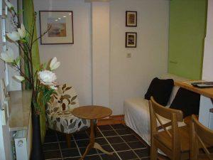 Sitzecke mit kleinem runden Holztisch, Sessel und Sofa