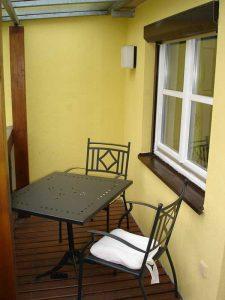 Holzbalkon mit Tisch und zwei Stühlen