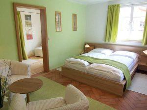 Überblick über Appartement 34 mit Bett, Sitzgruppe und Nebenzimmer