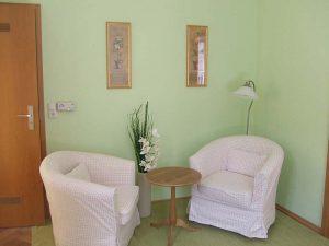 Zwei Sessel und kleiner runder Holztisch sowie Bilder an der Wand