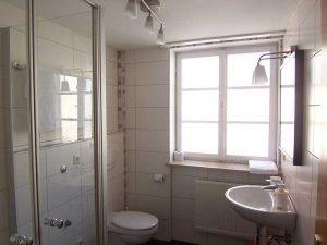 Bad - rechts Waschbecken mit Spiegel, links Toilette und Dusche