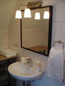 Bad im Appartement 36: Waschbecken, Spiegel und Beleuchtung